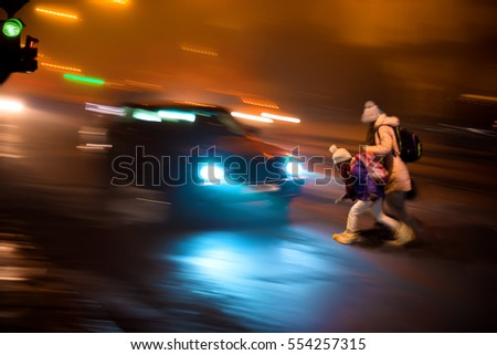 Children on zebra crossing at night. Dangerous situation with children and a car.  Intentional motion blur