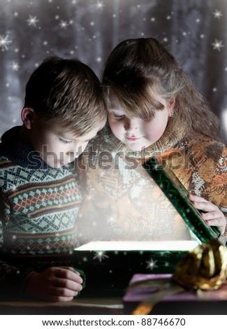 Children opening christmas magic present - stock photo