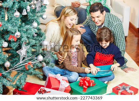 Children opening gifts at christmas eve while the family is watching - stock photo