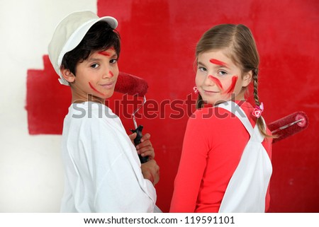 Children painting a wall red - stock photo