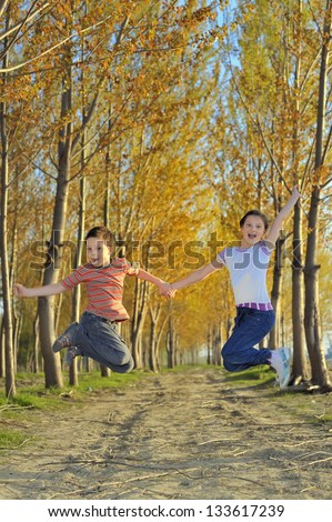 children play in forest in autumn time - stock photo