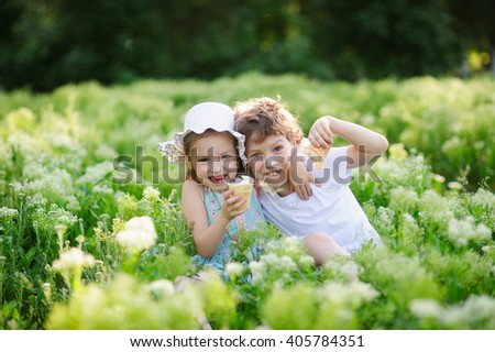 Children play together in the garden, eat ice cream and smile - stock photo