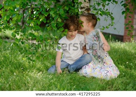 Children play together under the birch. The girl whispered something in the ear of a funny girl.