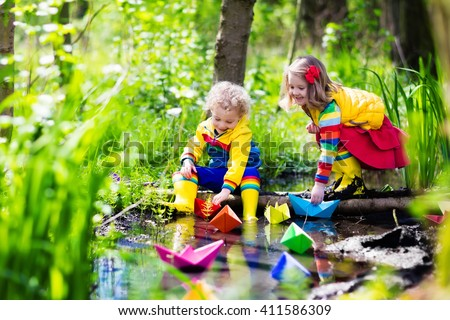 Children play with colorful paper boats in a small river on a sunny spring day. Kids playing exploring the nature. Brother and sister having fun at a forest stream. Boy and girl with toy boat and ship - stock photo