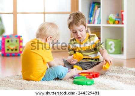 children play with educational toy in nursery - stock photo