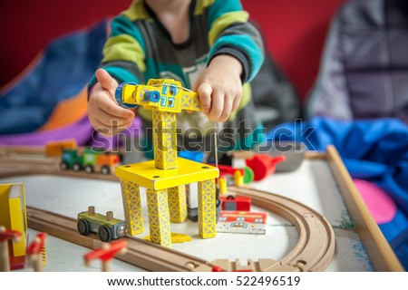 Children play with wooden toy, build toy railroad at home or daycare. Toddler boy play with crane, train and cars. Educational toys for preschool and kindergarten child. Cushioned furniture, chair bag