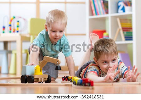 Children play with wooden train and build toy railroad at home, kindergarten or daycare - stock photo