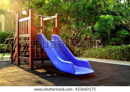Children playground under sunlight - blue slider - stock photo