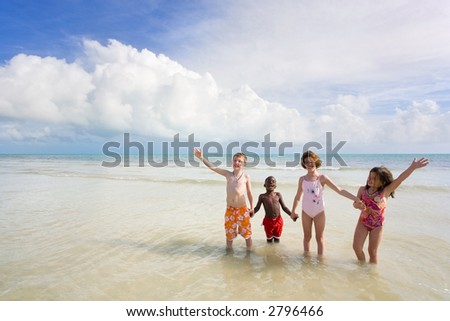 Children playing at the beach. - stock photo