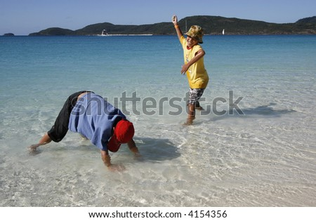 Children playing at the Whitehaven Beach - stock photo