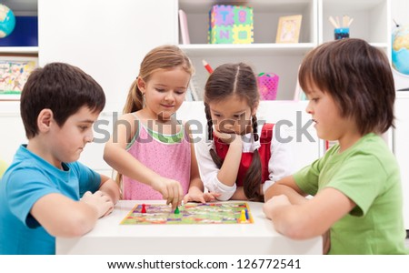 Children playing board game - sitting around a small table - stock photo