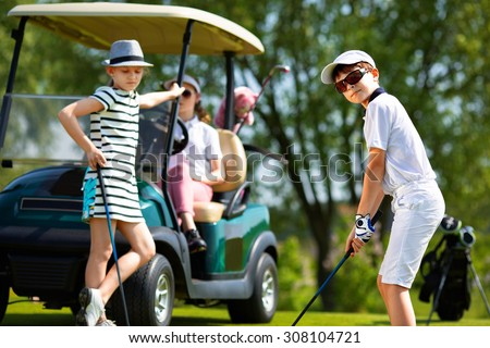 Children playing golf and taking part on kids competition in golf course at summer day - stock photo