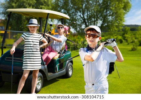 Children playing golf on kids competition in golf course at summer day - stock photo