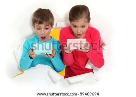 Children playing handheld computer games - stock photo