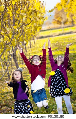 Children playing in the colorful fall leaves - stock photo