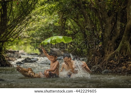 Children playing in the river - stock photo