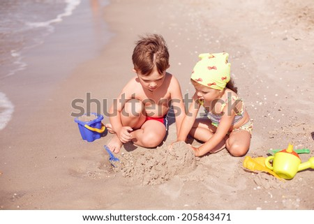 children playing in the sand on the seashore - stock photo