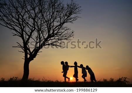 Children playing joyfully In the Sunset. - stock photo