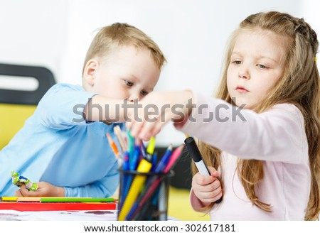Children playing. Little boy and girl spending time together. Brother and sister drawing something with multicoloured pencils. Girl choosing suitable colour from bunch of pencils. Family concept - stock photo