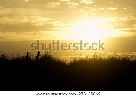 children playing on beach dunes at sunset silhouette - stock photo