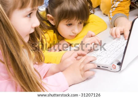 Children playing on laptop over white background - stock photo