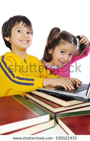 Children playing on laptop put on books - stock photo