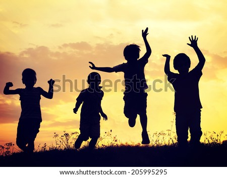 Children playing on summer sunset meadow - stock photo