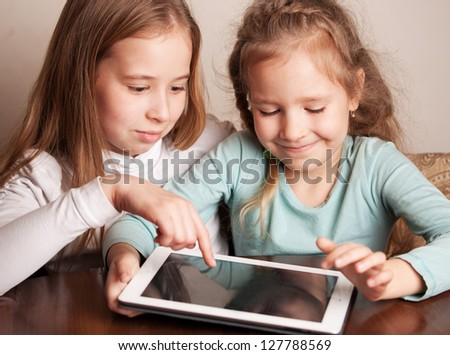 Children playing on tablet. Kids looking at computer - stock photo