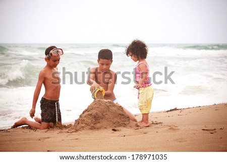 Children playing on the beach  - stock photo