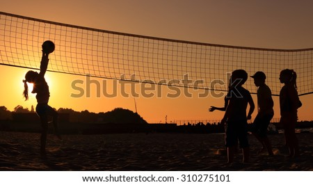 Children playing on the beach volleyball at sunset - stock photo