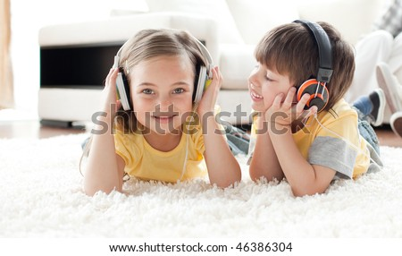 Children playing on the floor with headphones in the living room
