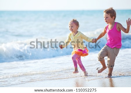 Children playing outdoors at the sea - stock photo