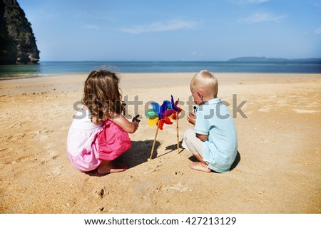 Children Playing Pinwheel Beach Summer Holiday Concept - stock photo