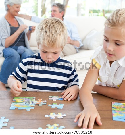Children playing puzzle in the living room - stock photo