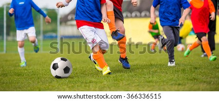 Children playing soccer football match. Sport soccer horizontal background. Young boys playing football soccer game. Running players in blue and red uniforms - stock photo