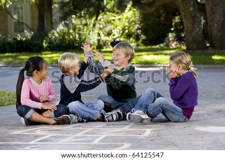 Children playing, teasing and laughing on driveway, ages 7 to 9. - stock photo