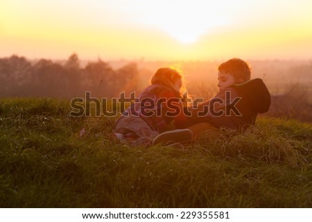 Children playing together in the warm light of a sunset, back lite situation. - stock photo