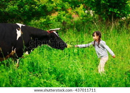 Children playing with a cow in the village. - stock photo