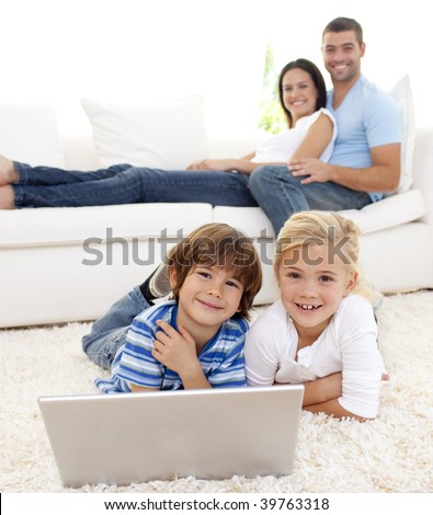 Children playing with a laptop on floor and parents lying on sofa - stock photo