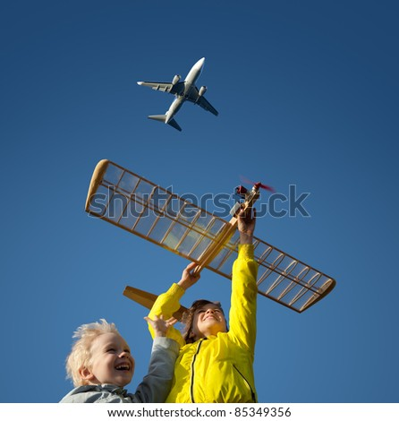 Children playing with a model glider in the background of an airplane that flies high into the blue sky. - stock photo