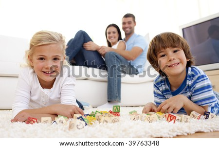 Children playing with alphabet cubes at home with parents on sofa - stock photo