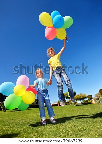 Children playing with balloons in park.