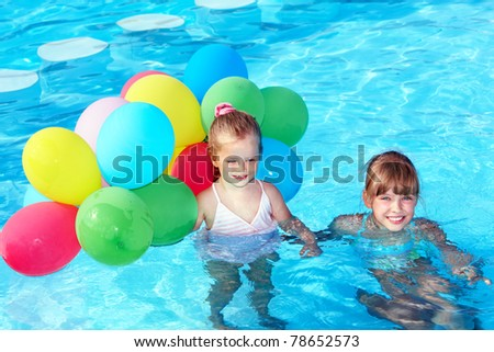 Children playing with balloons in swimming pool. - stock photo