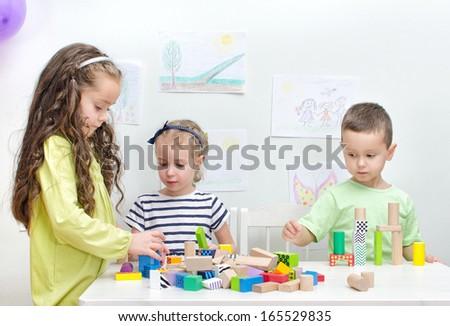 Children playing with blocks in kindergarten - stock photo
