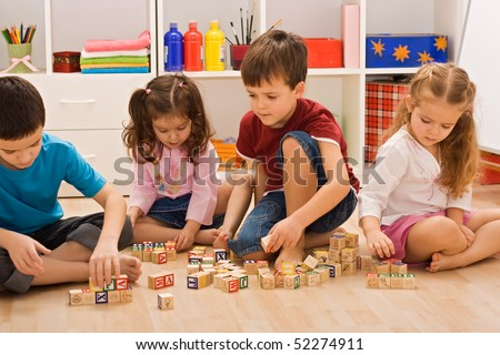 Children playing with blocks on the floor - stock photo