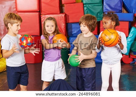 Children playing with different balls in gym of preschool - stock photo