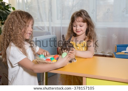 children playing with Easter Bunny.  Girls play with the Easter Bunny. Share with them colored eggs