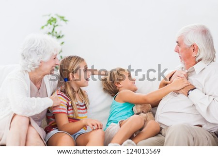 Children playing with grandparents on the couch - stock photo