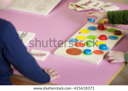 Children playing with homemade, do-it-yourself educational toys, arranging and sorting colors and sizes. Learning through experience concept, intelligence development, educational approach concept. - stock photo