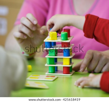Children playing with homemade, do-it-yourself educational toys, stacking and arranging colorful pieces. Learning through experience concept, gross and fine motor skills, back to school concept. - stock photo